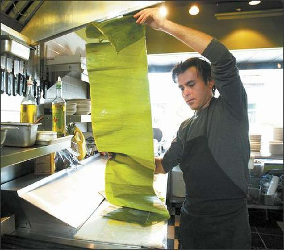 Alvaro Candela unrolls banana leaf to roast pork for tacos in a Mexican meal made for friends after hours at the Greek restaurant where he works. Photo: PAUL JOSEPH BROWN/P-I