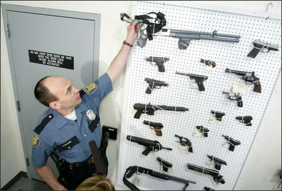 Donald Gallagher, an officer with the Seattle Police Department's evidence unit, shows some of the guns Tuesday that have been seized by Seattle police. Mayor Greg Nickels and police Chief Gil Kerlikowske called on state and federal legislators to pass tougher gun laws to keep firearms out of the hands of criminals. Photo: Scott Eklund/Seattle Post-Intelligencer