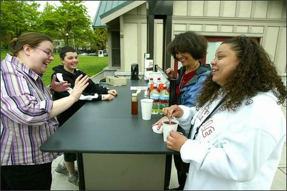 Tea cart supervisor Meg Higgins, left, and employee Blue McKeon chat with customers Denise Harnly and Wendy Leshane. A city program employs street youths to run the cart at Cal Anderson Park. Photo: Grant M. Haller/Seattle Post-Intelligencer