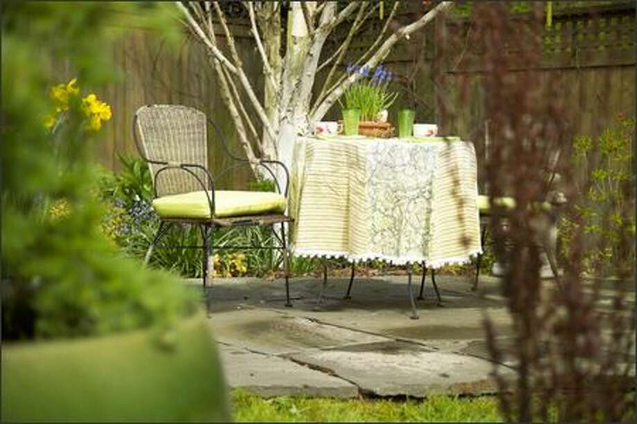 A cafe table with chairs under a Himalayan birch makes for an intimate seating area in this Seward Park garden belonging to Debra Prinzing and Bruce Brooks. Photo: Andrew Buchanan /