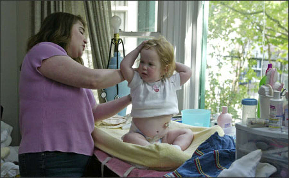 Pam Klein-Farrow helps her daughter, Samantha, get dressed. Samantha's parents found ways to keep their bond strong during her four months in intensive care.