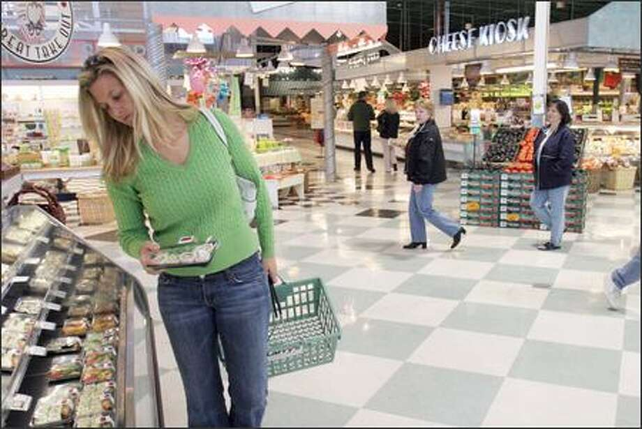 "Jessica Olsen shops for sushi Monday at Larry's Market in Kirkland. When Olsen heard that Larry's might close, she said, ""Darn. That's too bad."" She especially likes the help she gets at Larry's with wine selection. Larry's will ask a federal bankruptcy judge today to allow it to remain open and continue to pay its employees. Photo: MERYL SCHENKER/P-I"