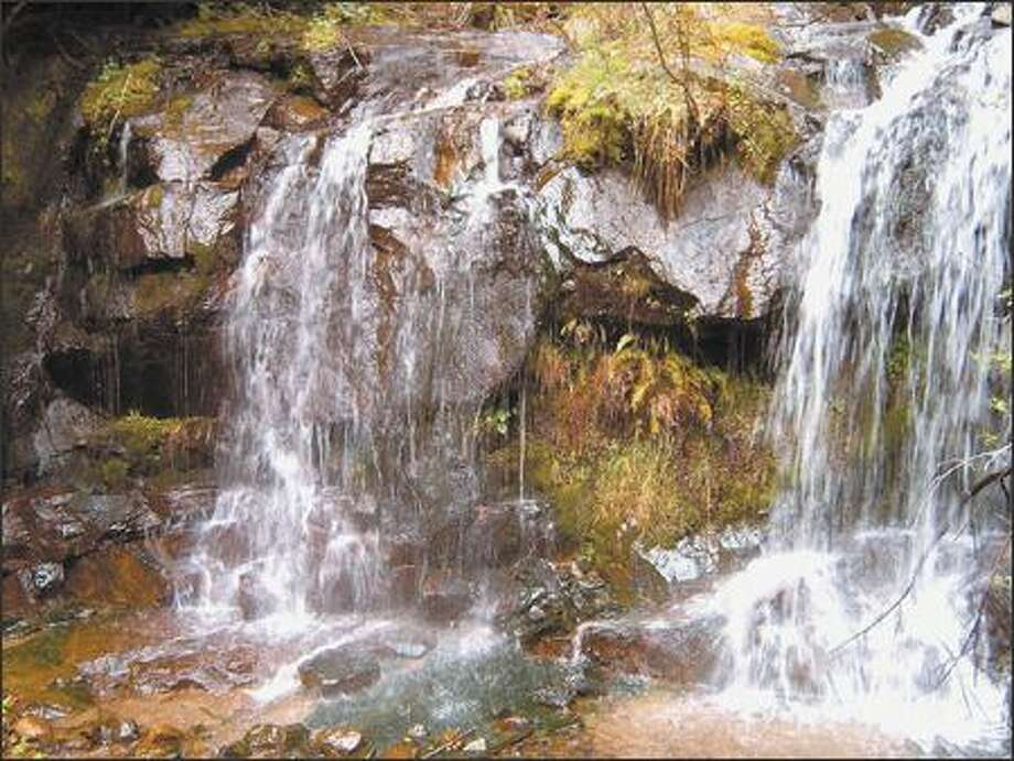 As the road zigzags up Bessemer Mountain, hikers will pass the long silver ribbon of a waterfall several times. At one point, the falls can be viewed as it pours through a culvert. Photo: KAREN SYKES