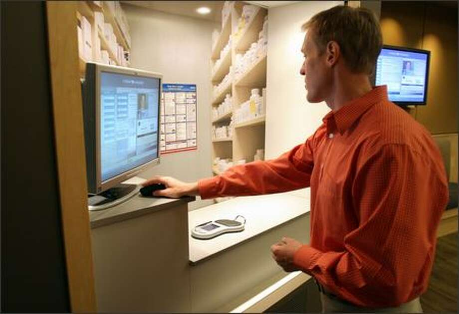 Tom Gruver, group product manager for Microsoft's Center for Information Work in Redmond, shows off the technology in a futuristic pharmacy. Photo: Meryl Schenker/Seattle Post-Intelligencer