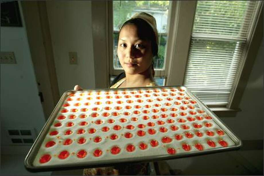 Toi Sennhauser holds a tray of her salty orange candy that represents her mother, partly because her mom eats oranges dipped in salt but mostly to signify her crusty exterior. Photo: SCOTT EKLUND/P-I