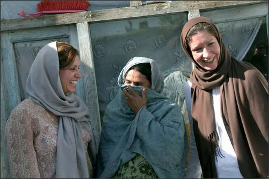 Americans Patty Quigley, right, and Susan Retik, left, whose husbands were killed in the Sept. 11, 2001, attacks, chat Thursday with an Afghan woman. Quigley and Retik decided to use their financial support to help war widows in Afghanistan. Photo: RODRIGO ABD/AP
