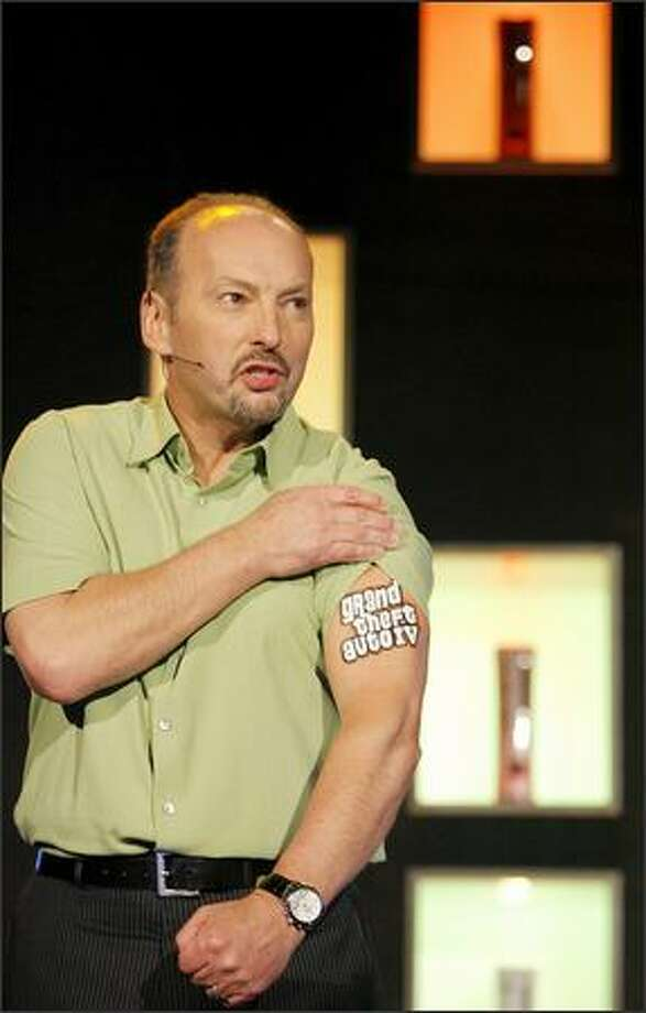 Peter Moore, the executive in charge of Microsoft's Xbox business, shows off a Grand Theft Auto 4 tattoo Tuesday before introducing a trailer for the video game at the 2006 E3 electronics expo in Los Angeles. Photo: / Associated Press