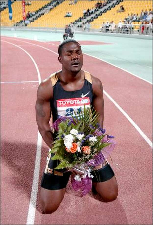 Justin Gatlin, the reigning Olympic and world champion, prays on the track after his record-breaking 9.76-second 100-meter run in Doha, Qatar, on Friday. Gatlin eclipsed Jamaican Asafa Powell's record. Photo: / Associated Press