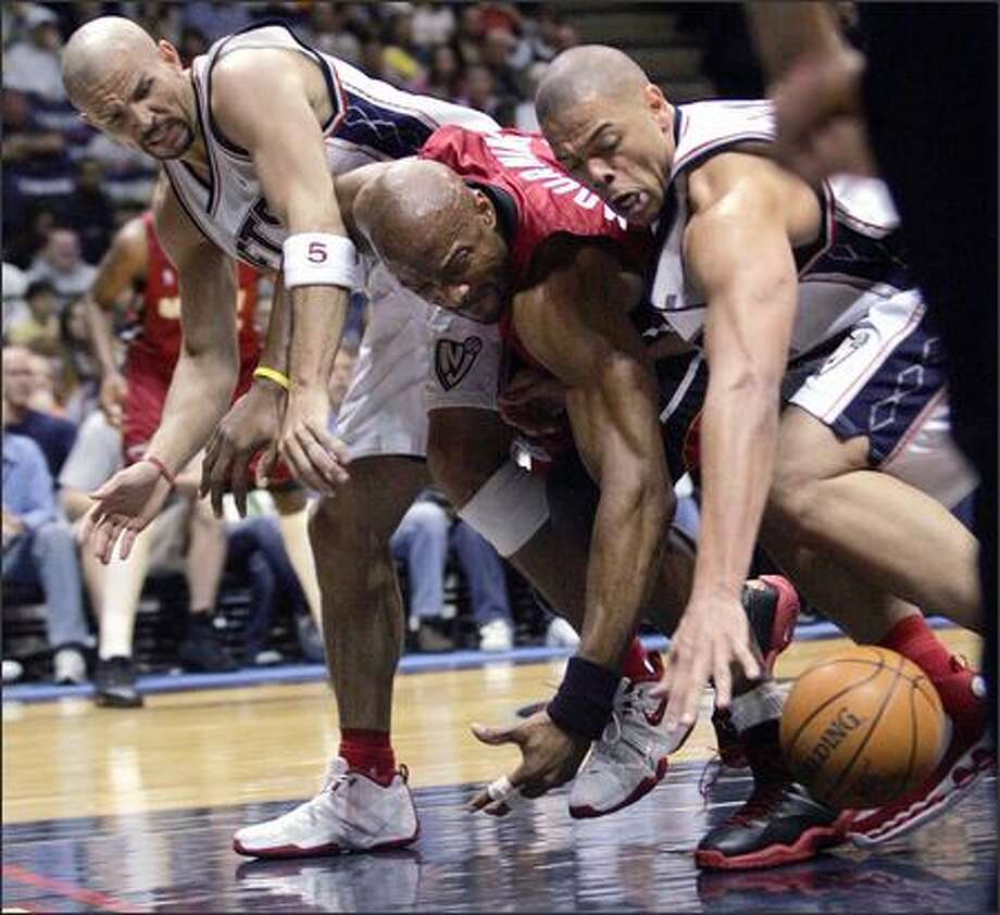 From left, Jason Kidd, Alonzo Mourning and John Thomas battle for a loose ball in East Rutherford, N.J. Photo: MEL EVANS/AP