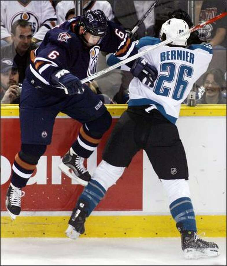 San Jose's Steve Bernier, right, slams into Edmonton's Jaroslav Spacek on Friday. Photo: / Associated Press