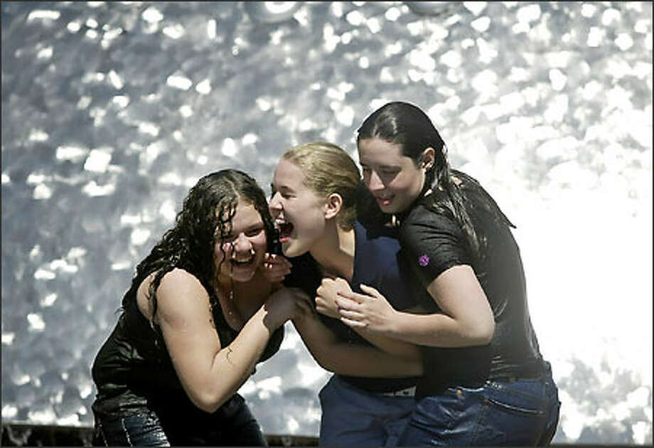 Dripping wet Chyna Copeland, left, and Kelsey Morton, drag a very dry Mary Elizabeth Howard, center, all of Redmond, for a dousing in the International Fountain at the Seattle Center on Tuesday. Photo: Jim Bryant/Seattle Post-Intelligencer