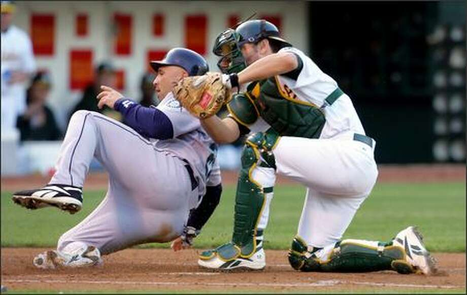 Oakland catcher Jason Kendall, right, tags out Raul Ibanez at home plate in the first inning. Ibanez was trying to score from second on Richie Sexson's single. Photo: / Associated Press