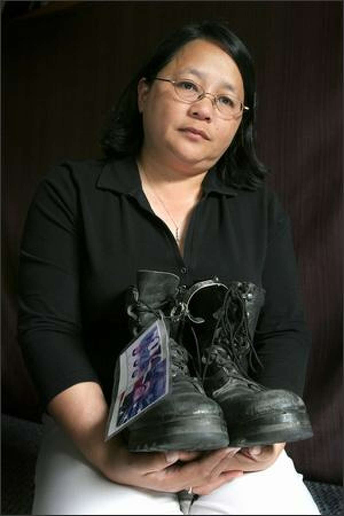 Doris Kent of Bellingham with her son's boots, with a picture and a bracelet threaded through the laces. Army Cpl. Jonathan Santos had just seven months to serve when he was killed by a roadside bomb in Iraq in October 2004.