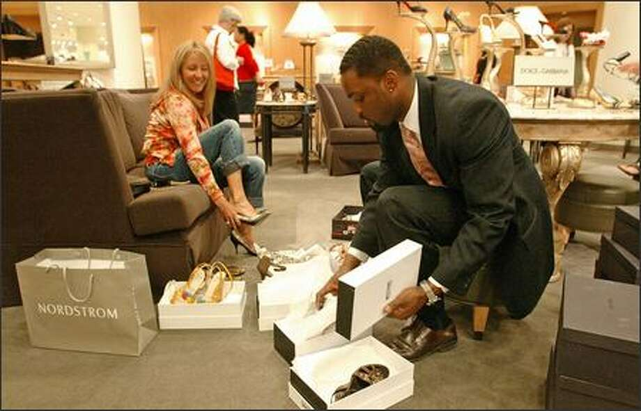 Sales associate Derek Henderson brings shoes to Kathleen Greer-Wilkes at the downtown Nordstrom. The retailer reported a jump in first-quarter profits Thursday. Photo: Gilbert W. Arias/Seattle Post-Intelligencer