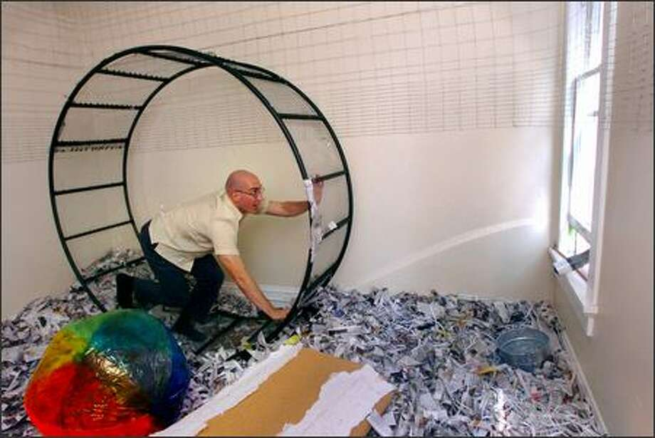 Luke Trerice tries out his hamster wheel Thursday in his Olympia apartment. The practical joke that turned his home into a hamster cage was payback for a 2004 joke on a friend. Photo: / Associated Press