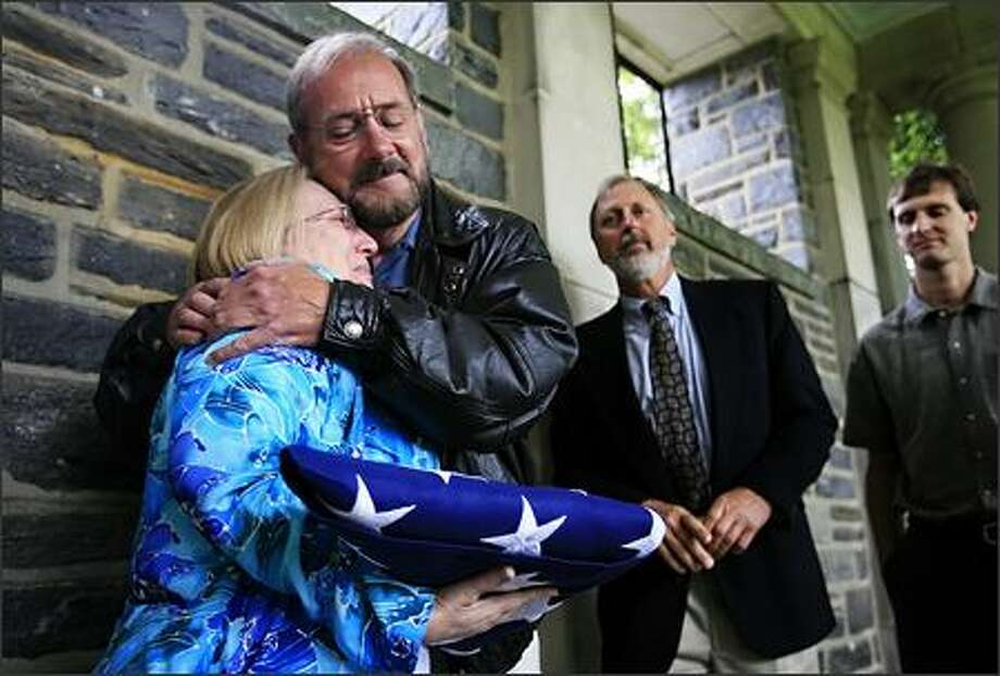 At the conclusion of a memorial Friday for World War II fighter pilot Lt. Kenneth W. Ambrose, his daughter, Kathleen Edwards, embraces Cye Laramie, as Steve Norris and his son, Chad Norris, look on. Photo: / Associated Press
