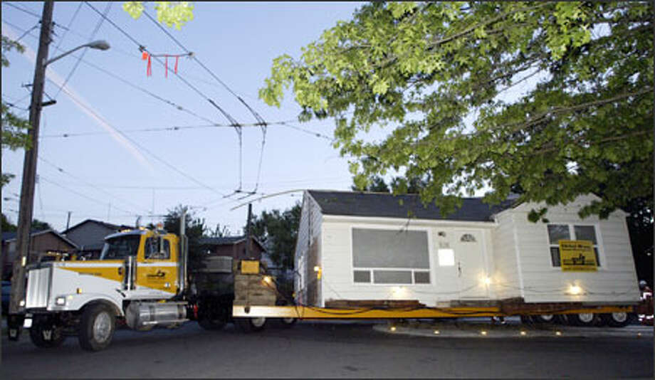 Driver Fred Watson of Nickel Bros. House Moving USA moves a house down 26th Avenue South to its new location early Sunday. Photo: Jim Bryant/Seattle Post-Intelligencer / Seattle Post-Intelligencer