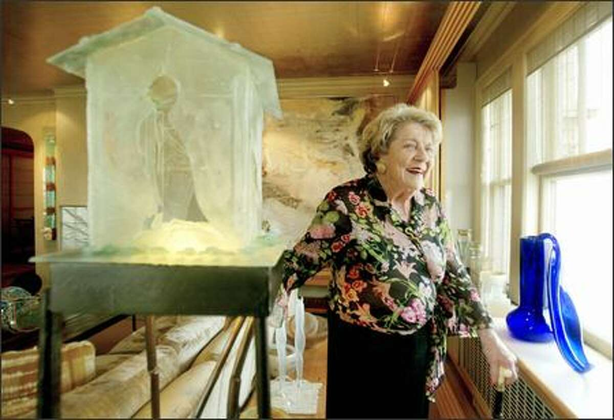 """Anne Gould Hauberg, seen in her art-filled First Hill condominium, has been a major force in the arts in Seattle for 50 years. At left is a sculpture by Mary White, """"Choosing To Listen to the Birds."""" On the window sill is a 1992 blown glass piece by Dale Chihuly, """"Cobalt Ikebana."""""""