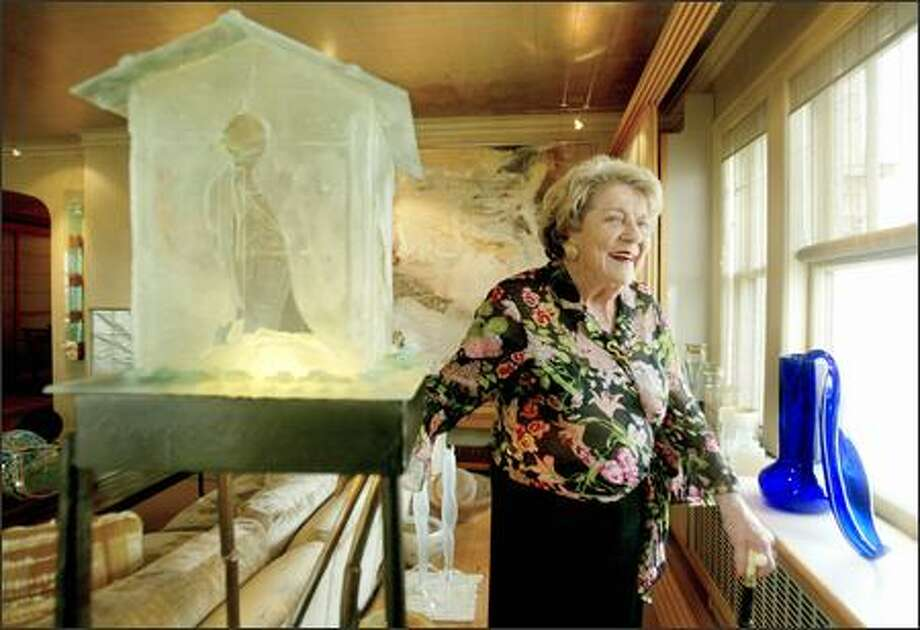 "Anne Gould Hauberg, seen in her art-filled First Hill condominium, has been a major force in the arts in Seattle for 50 years. At left is a sculpture by Mary White, ""Choosing To Listen to the Birds."" On the window sill is a 1992 blown glass piece by Dale Chihuly, ""Cobalt Ikebana."" Photo: PAUL JOSEPH BROWN/P-I"