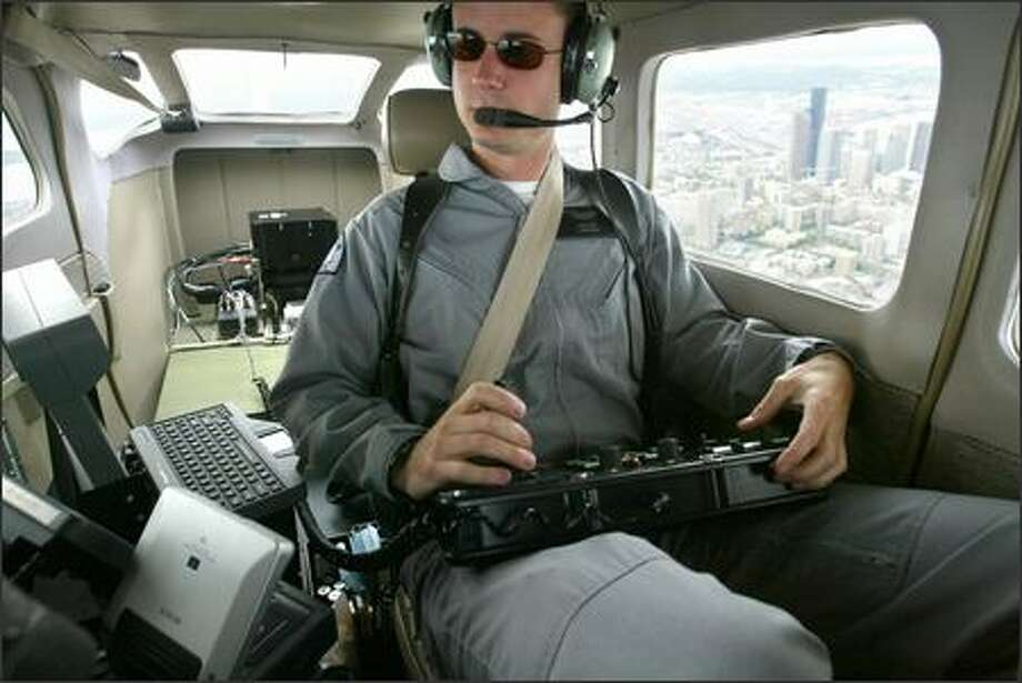 Trooper Scott Sweeney operates one of the new infrared camera systems from a State Patrol plane flying over downtown Seattle. Photo: Paul Joseph Brown/Seattle Post-Intelligencer