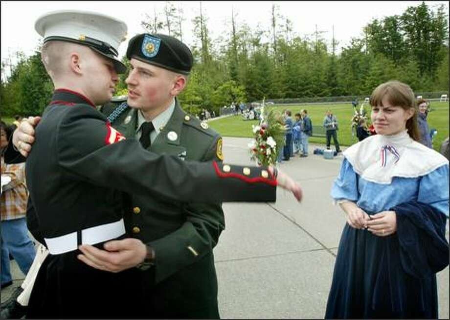 Marine Lance Cpl. Shawn Seeley of Covington is hugged by Army Spc. Arthur Bitzer after the Memorial Day ceremony at Tahoma National Cemetery. Seeley, 19, was seriously injured in Iraq in October when bombs flipped the Humvee he was riding in. Looking on is Bitzer's wife, Elizabeth. Photo: Dan DeLong/Seattle Post-Intelligencer