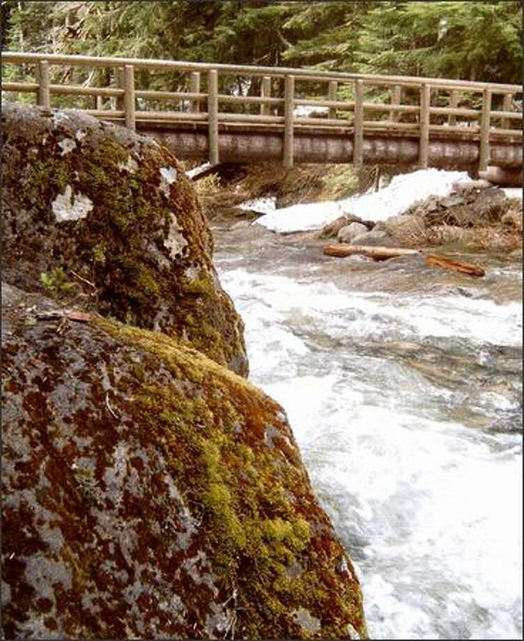 A picturesque footbridge spans Denny Creek, near the Denny Creek Slippery Slabs, a popular haunt in summer when the creek level is low and it's safe to play in the water. Photo: KAREN SYKES