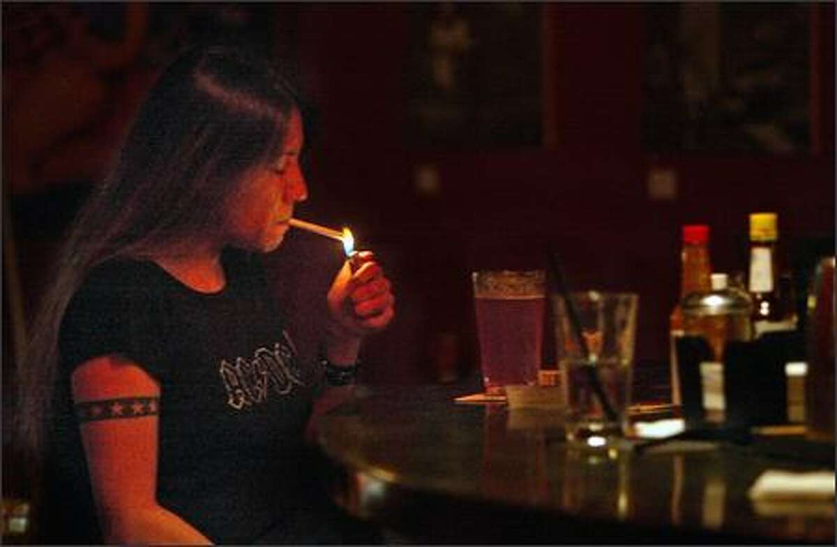 Alicia Kenan, 37, smokes in a Seattle bar after most of the other patrons have left. Smokers can still find spots to light up, inside.