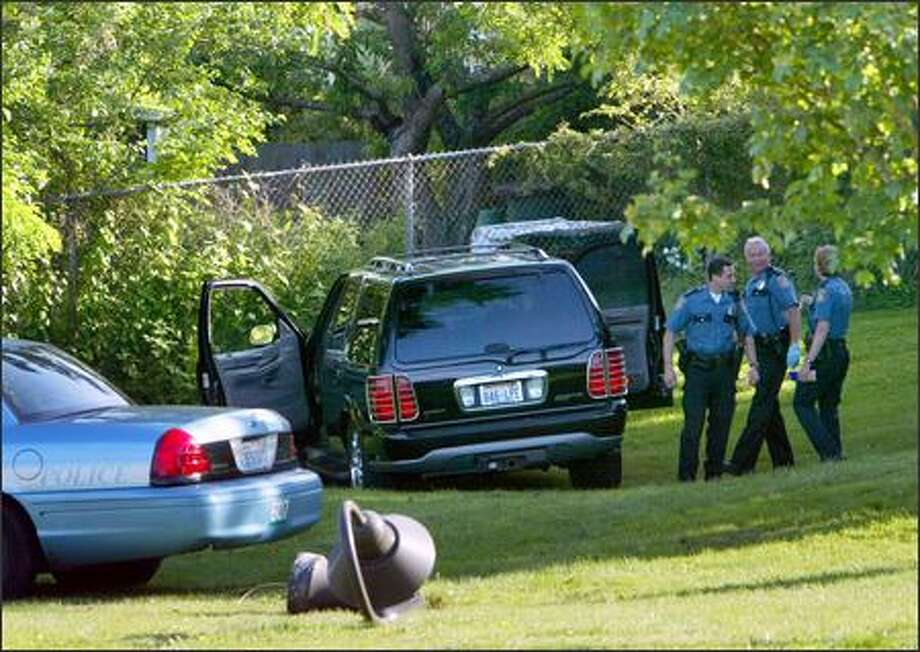 A light pole lies on the grass Tuesday as Seattle police officers investigate the fatal shooting of a man near Judkins Park. Photo: Grant M. Haller/Seattle Post-Intelligencer