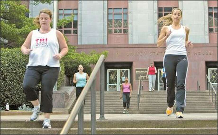 Brides-to-be jog down the stairs at the old federal courthouse building in Seattle. The women's workouts begin with eight grueling minutes on the stairs. Photo: KAREN DUCEY/P-I