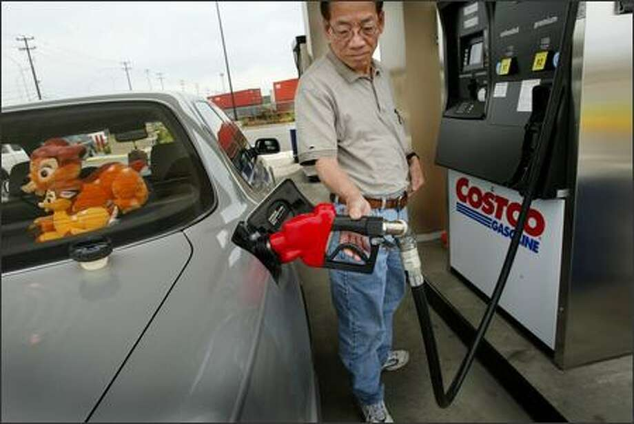 Cheng Saing fills his car Wednesday at Costco in Seattle. Rising gas prices reduced Costco's third-quarter earnings by about 2 cents per share, an official said. Photo: Joshua Trujillo/Seattle Post-Intelligencer