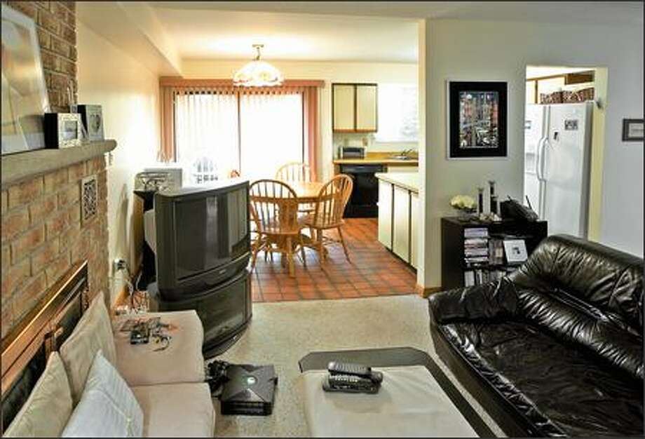 Separate, but equally dysfunctional: An outdated kitchen opened onto an outdated living room. Photo: / HGTV