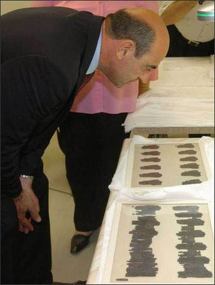 Greek Culture Minister Giorgos Voulgarakis examines the 2,400-year old Derveni scroll in Thessaloniki, Greece, Thursday. Photo: / Associated Press