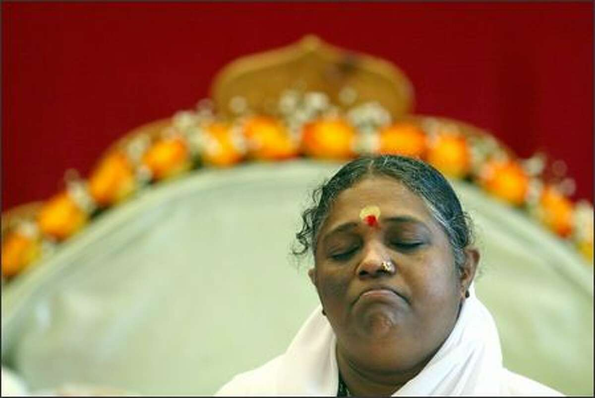 The Amma, or hugging saint (whose full name is Sri Mata Amritanandamayi Devi), meditates with hundreds of followers at the Seattle Center on Thursday.