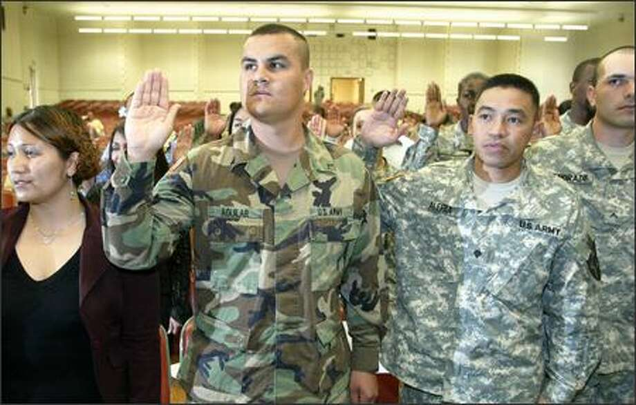 Army Pvt. Cesar Aguilar, center left, and others take the oath of allegiance to become U.S. citizens on Friday at Fort Lewis. Photo: Gilbert W. Arias/Seattle Post-Intelligencer