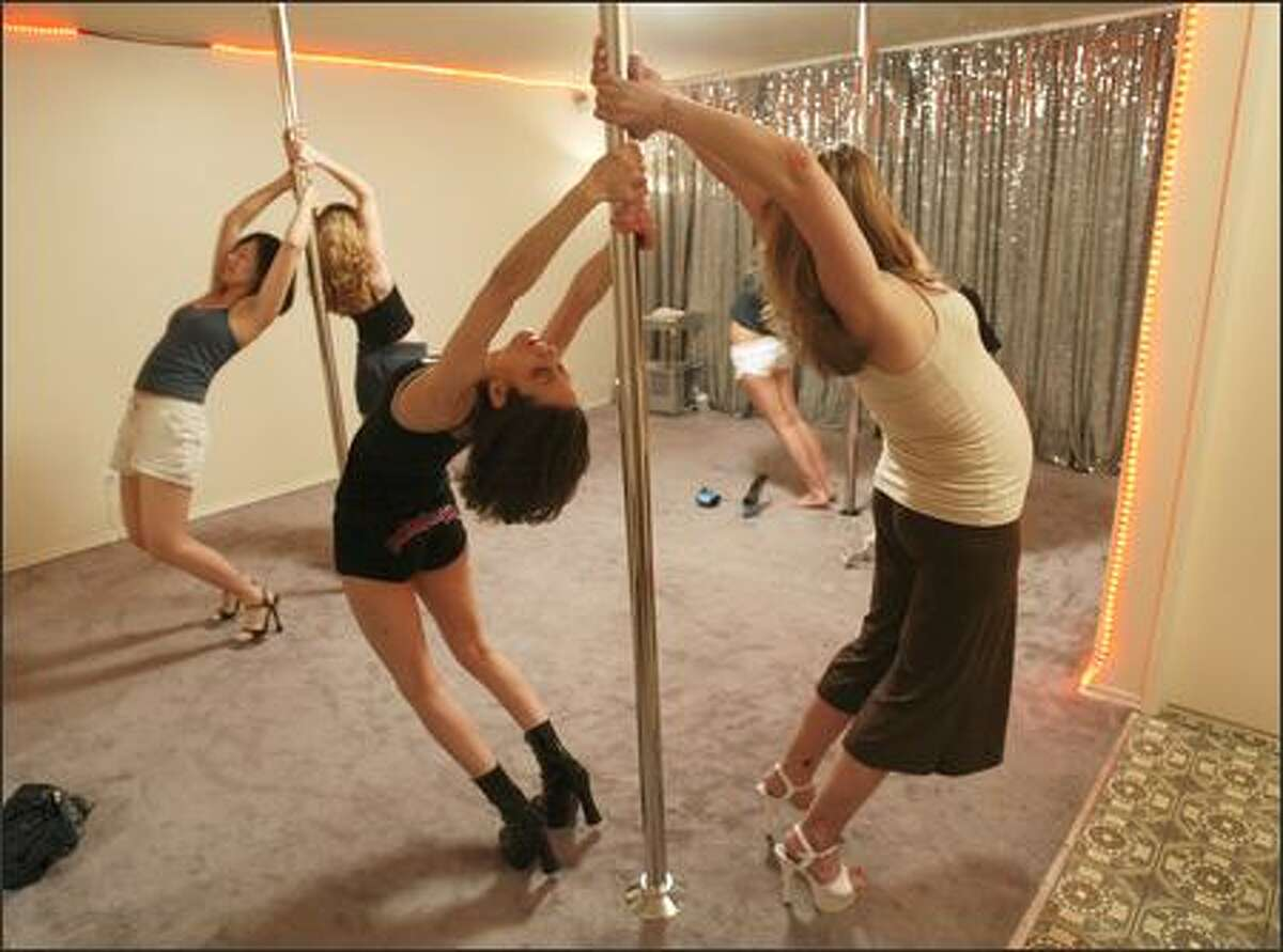 """Krisha CatZen, center front, leads her pole-dancing class in stretching exercises. The former go-go dancer says, """"This is about raising self-esteem, fitness and building strength in your arms and abs."""""""