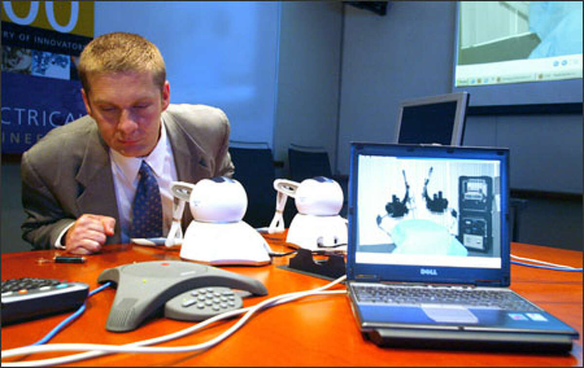 University of Cincinnati surgeon Timothy Broderick takes part in a test in Seattle on Friday of equipment to remotely treat injured soldiers. In front of him are devices that enable users to manipulate robotic arms during a remote surgical procedure.