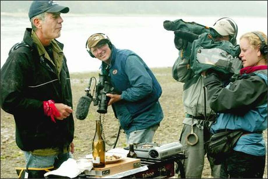 Anthony Bourdain, left, samples geoduck sauteed in white wine on a beach near Shelton as his three-person TV crew captures the moment for the Travel Channel. Photo: Paul Joseph Brown/Seattle Post-Intelligencer