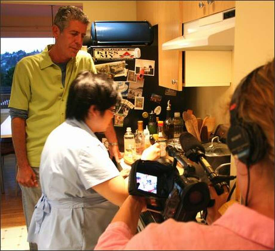 """Anthony Bourdain and a camera person sandwich Hsiao-Ching Chou in her kitchen as she prepares pot stickers for a segment of """"Anthony Bourdain: No Reservations."""" Photo: Eric Riddle/Special To The Post-Intelligencer"""