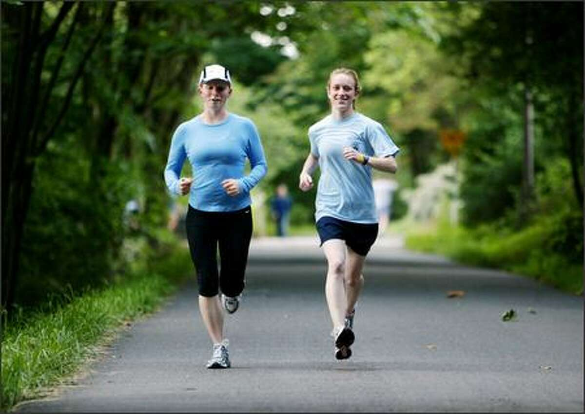 Heather Ann Brauer, right, of Seattle runs with Stephanie Miller of Bellevue on the Burke-Gilman Trail on Tuesday. Miller responded to Brauer's online ad for a running partner. Research has shown that workout pairs are more likely to go farther at a quicker clip than solo exercisers.