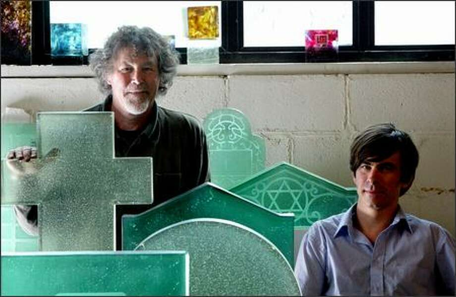 Greg Lundgren, right, and Jim Nelsen, who own Lundgren Monuments, display some of the glass headstones and other items they've made at their shop in Fremont. Photo: Karen Ducey/Seattle Post-Intelligencer