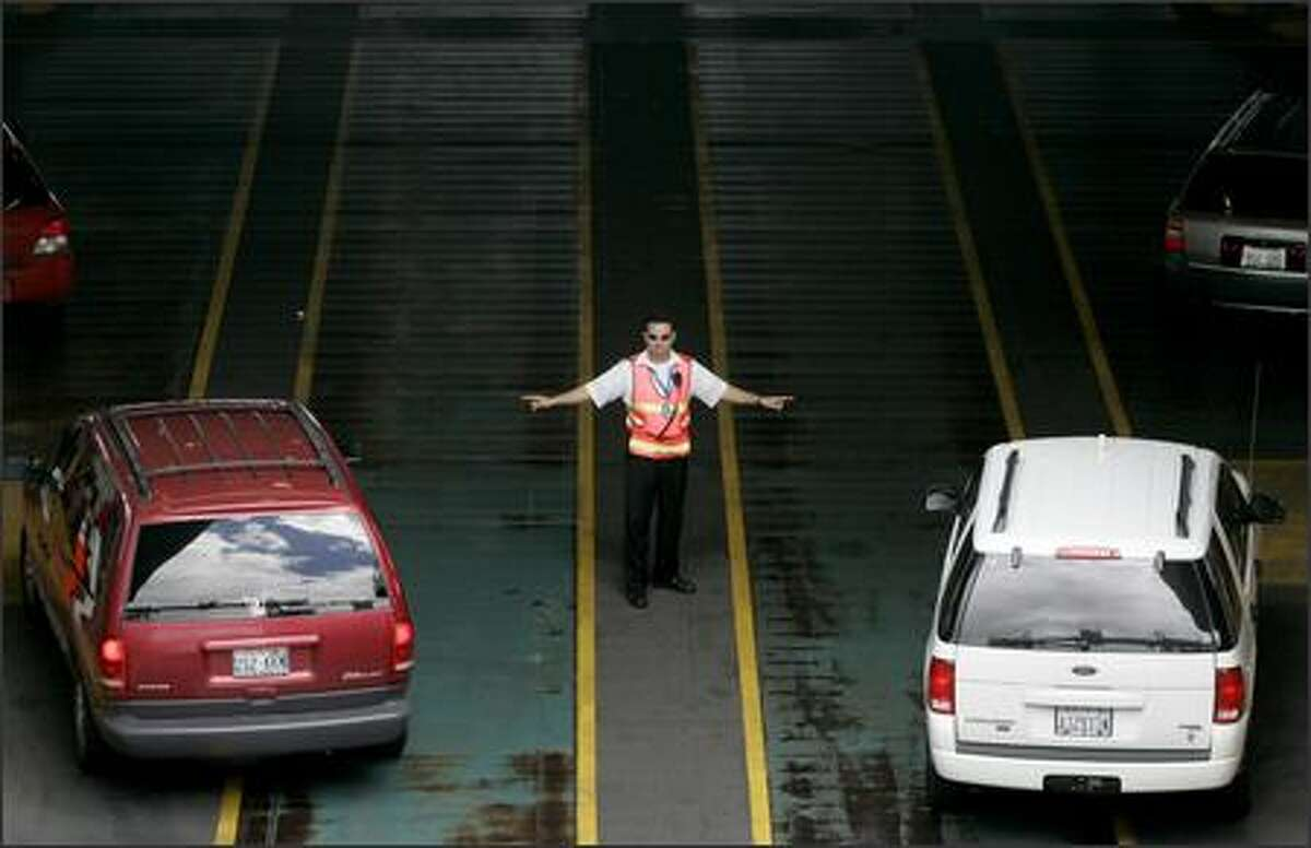 Second mate Frank, who didn't want his last name used, directs traffic boarding a ferry from Bainbridge Island to Seattle Thursday.