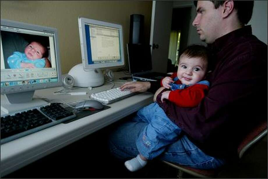 Bellevue stay-at-home dad Patrick Lindsay works on his blog, Puppybark, with 5-month-old son Andrew offering inspiration. Photo: Paul Joseph Brown/Seattle Post-Intelligencer