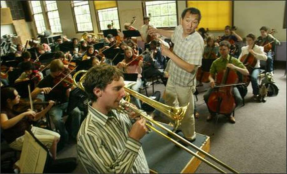 Marcus Tsutakawa, director of the Garfield High School orchestra, rehearses with his students June 7. Current and former students and others are planning a tribute to him. Photo: Karen Ducey/Seattle Post-Intelligencer