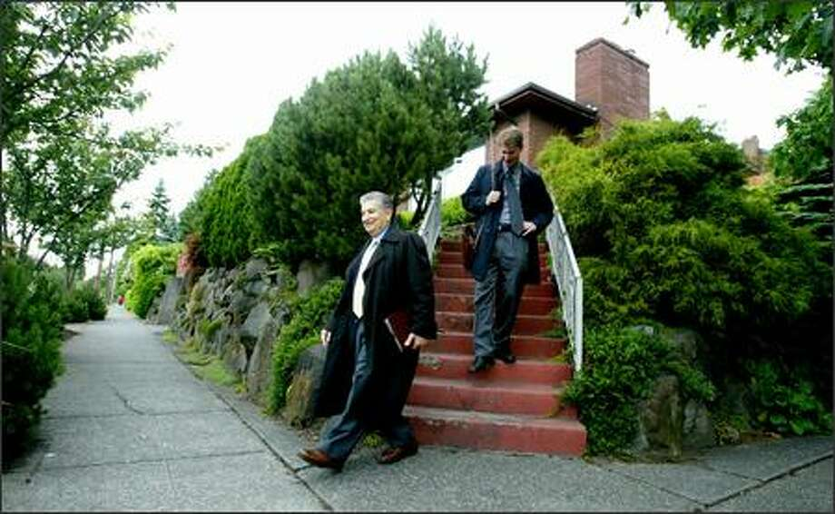 Jehovah's Witnesses Peter Michas and Chris Mahla invite residents of a North Seattle neighborhood to the faith's upcoming convention at the Tacoma Dome. Photo: Paul Joseph Brown/Seattle Post-Intelligencer