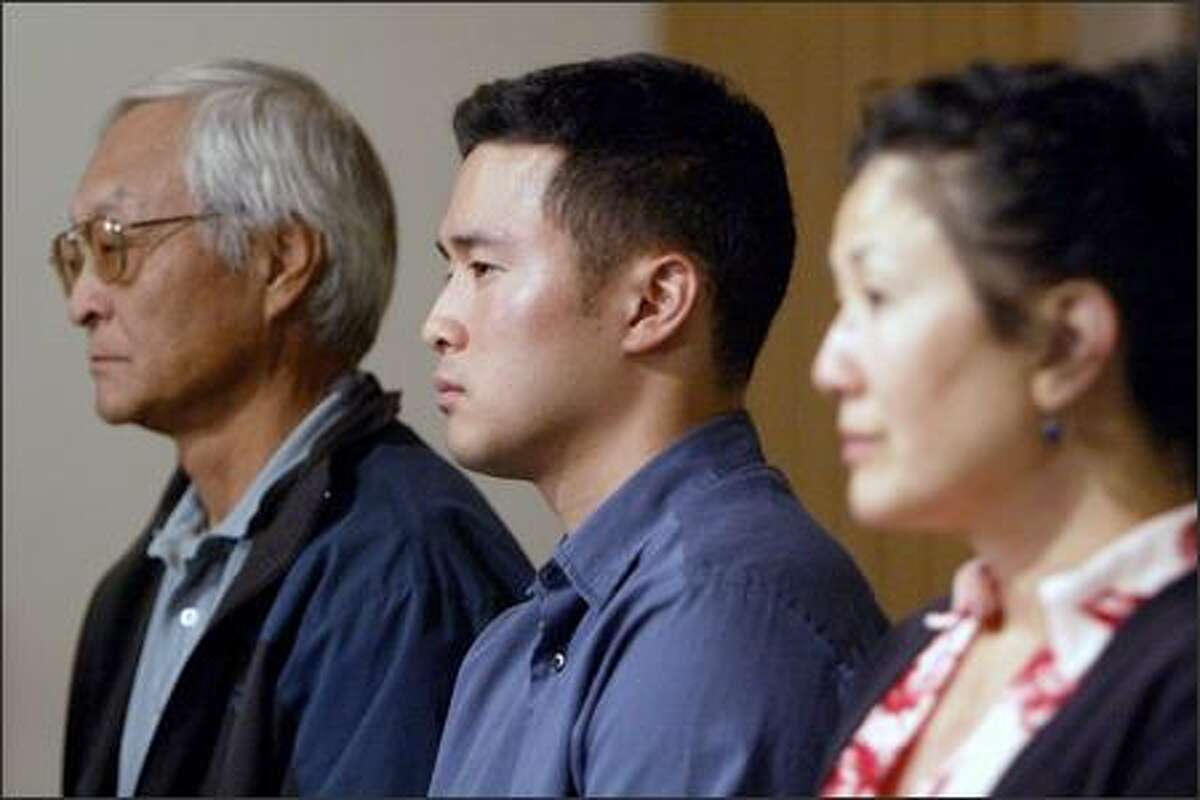 Lt. Ehren Watada is flanked by his father, Robert Watada, and his mother, Carolyn Ho, at Seattle's University Lutheran Church Monday.