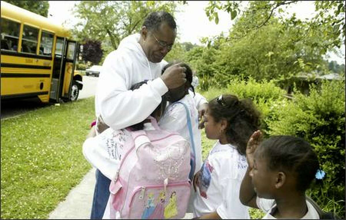 Principal Barry Dorsey of Martin Luther King Jr. Elementary School bids farewell to students Wednesday as they board buses on the final day of classes.