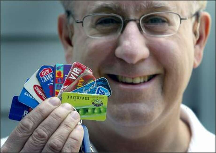 Keith Gormezano shows club cards from various grocery stores. By playing his cards right, he stays ahead in the privacy game. Photo: Joshua Trujillo/Seattle Post-Intelligencer