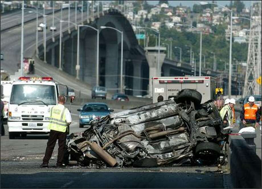 A car traveling eastbound over the West Seattle Bridge early Thursday struck the median at the First Avenue offramp, flipped and burst into flames. Three were killed. Photo: Steve Shelton/Special To The P-I