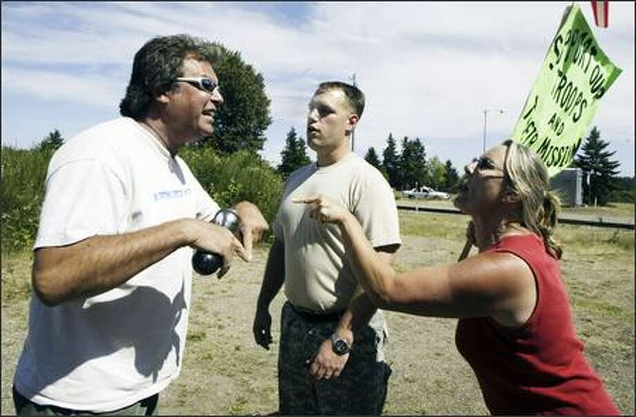Anti-war protester Brad Krull, top left, and Shelley Weber exchange words during a demonstration Tuesday in support of Lt. Ehren Watada and two others who have refused orders to deploy to Iraq. An identified soldier stands between the two. Photo: Jim Bryant/Seattle Post-Intelligencer