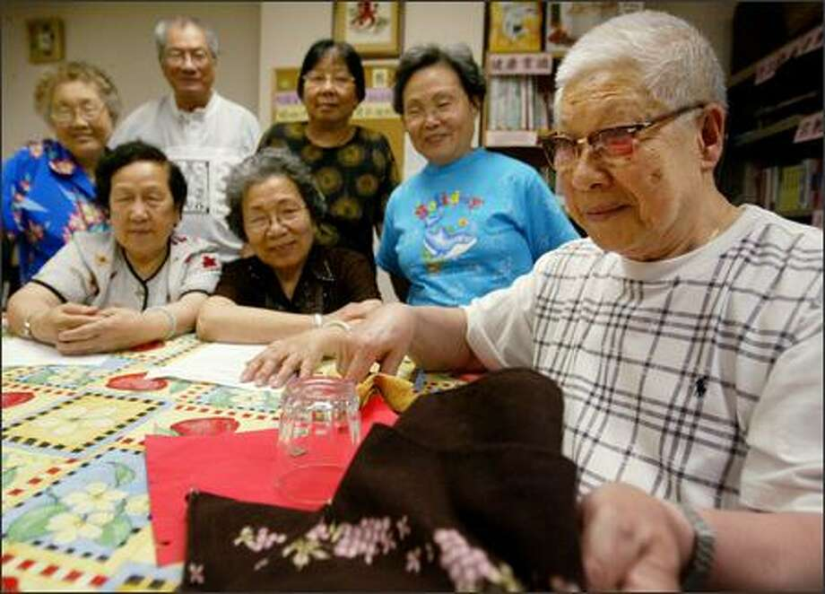 Ji Quan Pan, 81, teaches a magic class at Sunshine Garden Senior Day Care Center, run by the Chinese Infor- mation and Service Center. The Seattle Foundation, which is in its 60th year supporting philan- thropy, said the CISC contributes to a healthy sense of community. Photo: Paul Joseph Brown/Seattle Post-Intelligencer